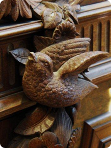Detalj av höger klavsida med fågel i blomstergirland.