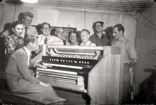 Martin Axelsson omgiven av arbetarna vid Östlind & Almquists orgelavdelning.